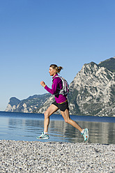 Italy, Mid adult woman jogging by Lake Garda - MIRF000520
