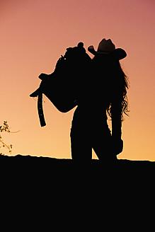 USA, Texas, Cowgirl holding saddle - ABAF000449