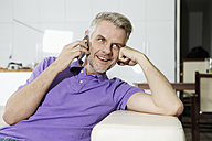 Germany, Berlin, Mature man sitting on sofa and talking on mobile phone, smiling - SKF001129