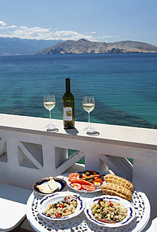 Croatia, Table laid with food in restaurant, adriatic sea in background at Baska - WWF002536