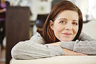 Germany, Duesseldorf, Mature woman relaxing on sofa, smiling - STKF000076