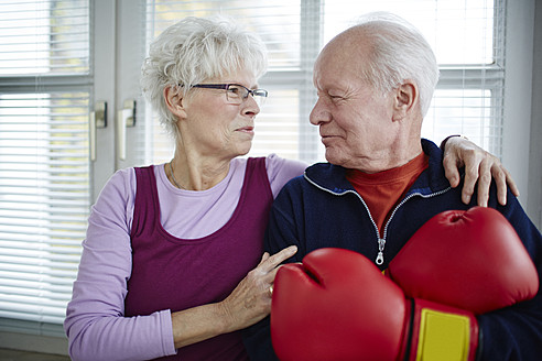 Germany, Duesseldorf, Senior couple with boxing glove, smiling - STKF000083
