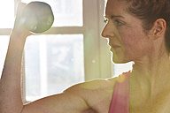 Germany, Duesseldorf, Mature woman exercising with barbell - STKF000098