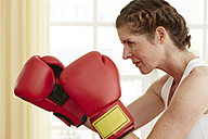 Germany, Duesseldorf, Mature woman with boxing glove, close up - STKF000100