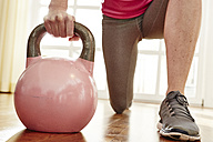 Germany, Duesseldorf, Mature woman exercising with kettlebell - STKF000107