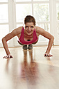 Germany, Duesseldorf, Mature woman doing push ups at home - STKF000112