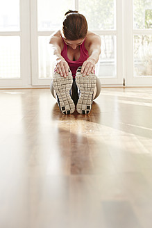Germany, Duesseldorf, Mature woman exercising at home - STKF000117