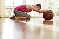 Germany, Duesseldorf, Mature woman exercising with medicine ball - STKF000127
