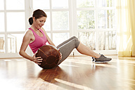Germany, Duesseldorf, Mature woman exercising with medicine ball - STKF000131