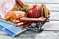 Studio, variety of ham, sausages, tomatoes, rosemary and bread, served on tray - MAEF005289