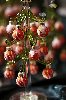 Germany, Small glass christmas tree with christmas baubles, close up - HOHF000007