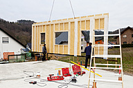 Europe, Germany, Rhineland Palatinate, Men fixing crane swivels wall of prefabricated house over foundation - CSF016028