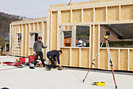 Europe, Germany, Rhineland Palantinate, Men installing and fixing wooden walls of prefabricated house - CSF016036