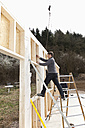 Europe, Germany, Rhineland Palantinate, Men installing and fixing wooden walls of prefabricated house - CSF016039
