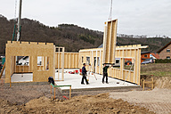 Europe, Germany, Rhineland Palantinate, Men installing and fixing wooden walls of prefabricated house - CSF016042