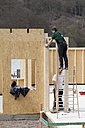 Europe, Germany, Rhineland Palantinate, Men installing and fixing wooden walls of prefabricated house - CSF016044