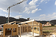 Europe, Germany, Rhineland Palantinate, Man installing and fixing wooden walls of prefabricated house - CSF016067