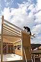Europe, Germany, Rhineland Palantinate, Man installing and fixing wooden walls of prefabricated house - CSF016069