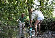 Austria, Teenage girl and boy splashing water in stream - WWF002744