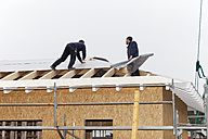 Europe, Germany, Rhineland Palatinate, Workers roofing on house - CSF016098