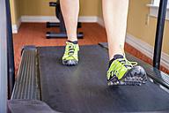 USA, Texas, Rockport, Mature woman running on treadmill - ABAF000650
