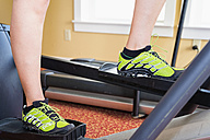USA, Texas, Rockport, Mature woman working out on elliptical cross trainer in gym - ABAF000651