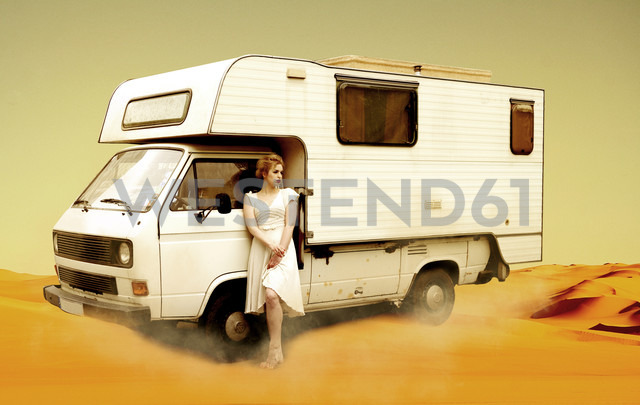 Germany, Berlin, Young woman standing next to camping bus in desert - NG000011 - Nadine Ginzel/Westend61