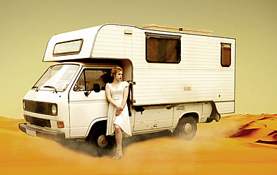 Germany, Berlin, Young woman standing next to camping bus in desert - NG000011