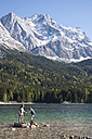 Germany, Bavaria, Boy and girl playing on Lake Eibsee with Zugspitze mountain in background - UMF000573