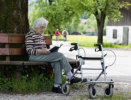Austria, Senior woman sitting on bench and reading book - WWF002465