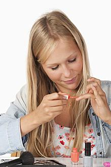 Teenage girl applying nail polish, close up - WWF002475