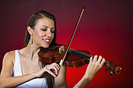 Young woman playing violin, smiling - ABAF000670