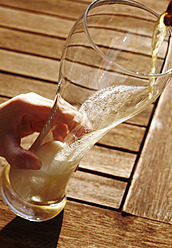 Germany, Bavaria, Human hand pouring wheat beer in glass, close up - JTF000265