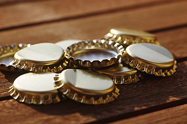 Germany, Beer bottle caps on table, close up - JTF000269