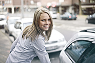 Germany, Duesseldorf, Young woman getting in to car, smiling, portrait - MF000457