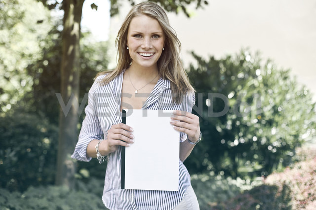 Germany, Duesseldorf, Young woman holding folder, smiling, portrait - MF000443 - Mareen Fischinger/Westend61