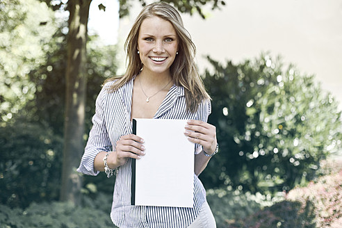Germany, Duesseldorf, Young woman holding folder, smiling, portrait - MF000443