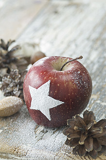 Christmas apple with snow star, pine cones, almonds and hazelnuts on table - ASF004756