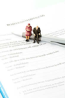 Figurines sitting on pen with advance directive form, close up - MAEF005553