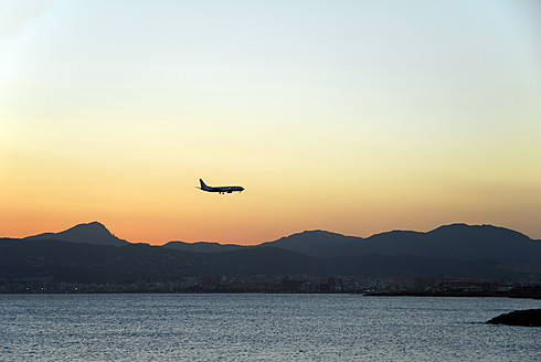 Spain, Mallorca, Palma, Airplane landing over bay - MIZ000149