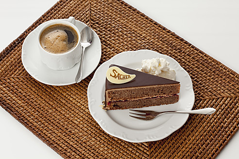 Plate of Sachertorte slice with coffee on straw mat, close up - CSF016290