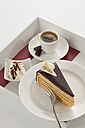 Slice of Herrentorte with whipped cream and cup of coffee in tray - CSF016299