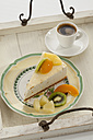 Slice of Yoghurt Maracuja Cake on plate with cup of coffee in tray, close up - CSF016314