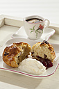 Cranberry scones with whipped cream and cup of coffee in tray, close up - CSF016341