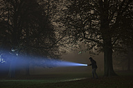 Germany, Munich, Young man with torch in foggy night - FL000182