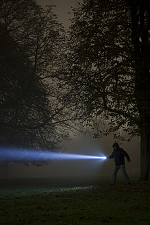Germany, Munich, Man lighting spooky tree with torch in foggy night - FL000154