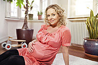 Germany, Bonn, Portrait of pregnant woman holding her belly, smiling - MFF000489