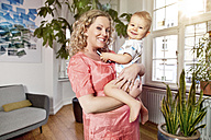 Germany, Bonn, Pregnant mother in living room with her son, smiling, portrait - MFF000492