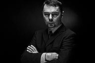 Portrait of mature man against black background, close up - MAE005679