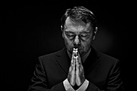 Mature man in full suit praying against black background, close up - MAE005685